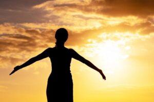 夕焼けで深呼吸をしている女性のイメージ