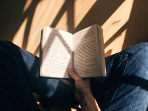 光の差す部屋で座りながら洋書を読むイメージ