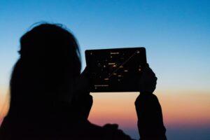 夕焼けに女性がタブレットを持つイメージ
